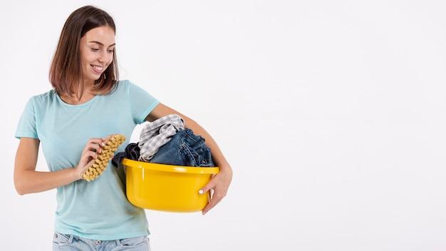 Medium shot smiley woman with brush and laundry basket