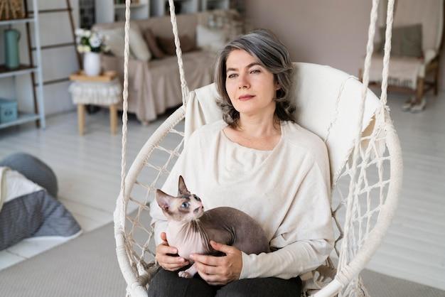Улыбающаяся женщина среднего выстрела с кошкой