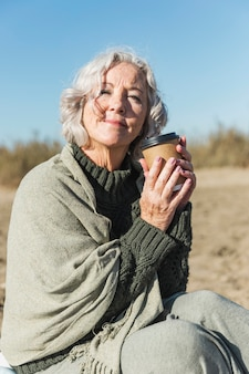 Medium shot smiley woman with coffee cup