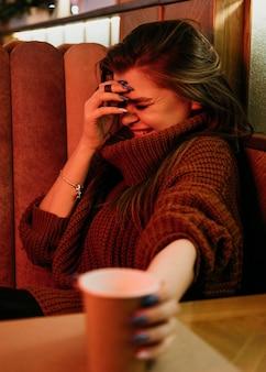 Donna di smiley colpo medio con tazza di caffè