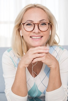 Medium shot smiley woman with glasses and headphones
