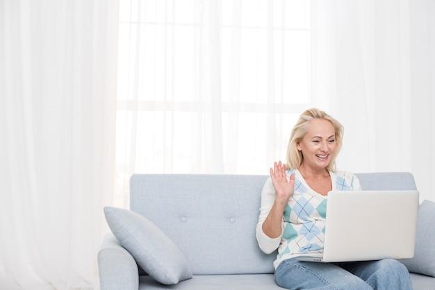 Medium shot smiley woman with laptop waving