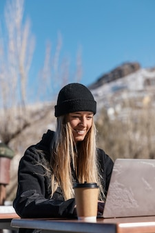 Улыбающаяся женщина среднего выстрела с ноутбуком Бесплатные Фотографии