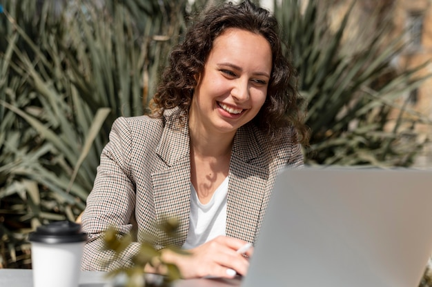 Улыбающаяся женщина среднего выстрела с ноутбуком