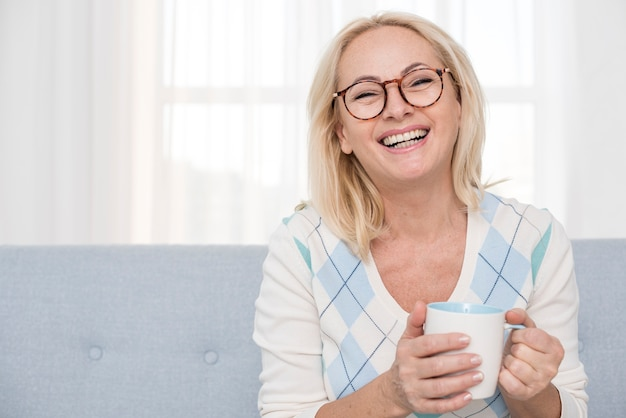 Medium shot smiley woman with mug on the couch