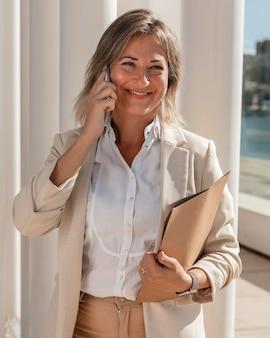 Donna di smiley colpo medio con il telefono