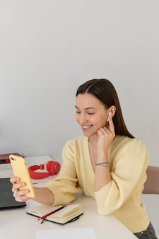 Medium shot smiley woman with phone