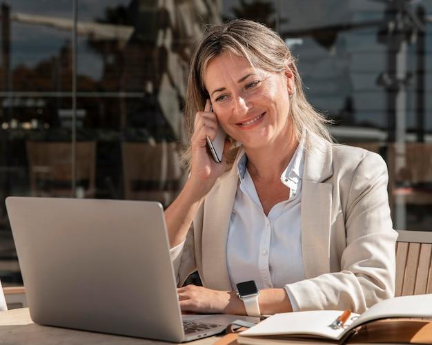 屋外で働くミディアムショットの笑顔の女性