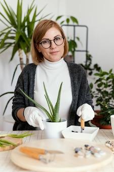 Donna di smiley colpo medio che lavora con i guanti