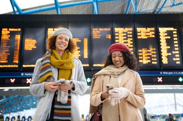 Donne sorridenti a colpo medio alla stagione invernale dell'aeroporto