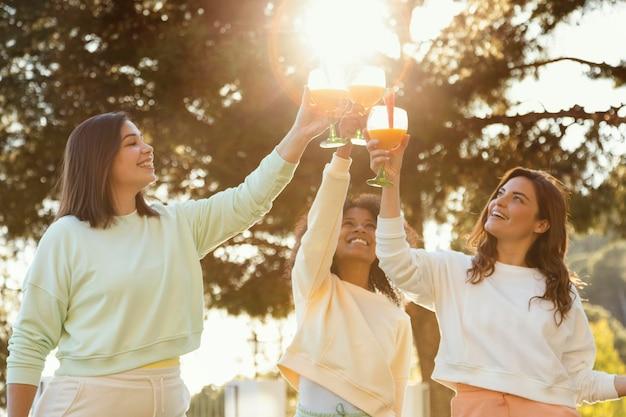 ミディアムショットのスマイリー女性が飲み物をチリンと鳴らす