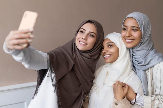 Donne sorridenti a colpo medio che prendono selfie