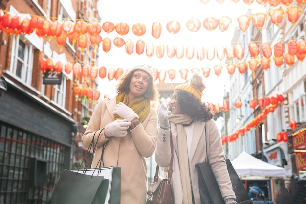 街を歩くミディアムショットのスマイリー女性