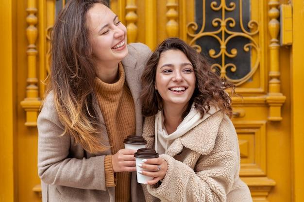 コーヒーカップとミディアムショットのスマイリー女性