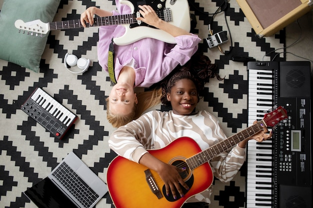 Улыбающиеся женщины среднего размера с гитарами на полу
