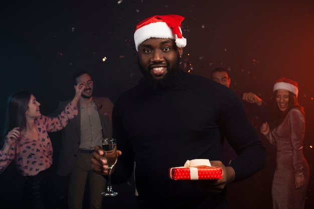 Medium shot of smiling man drinking champagne at new years party