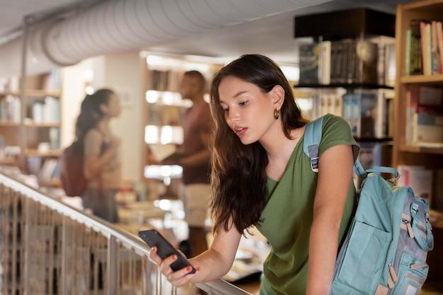 Студент среднего кадра, держащий смартфон