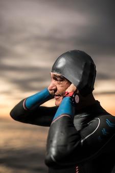 Пловец среднего роста надевает кепку