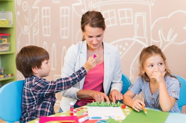 중간 샷 교사 돕는 아이들