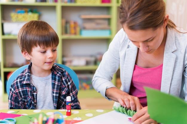 Учитель среднего кадра помогает маленькому мальчику