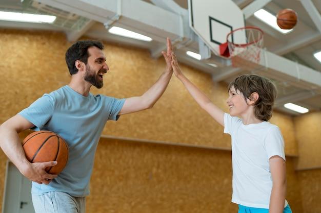 Medium shot teacher and kid high five
