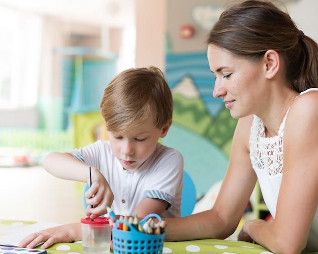 Medium shot teacher and kid painting