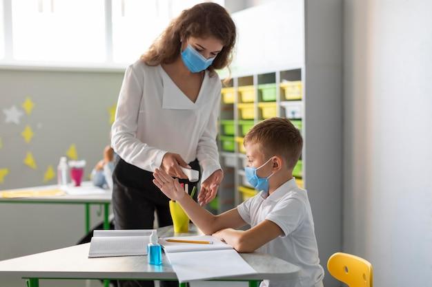 Insegnante di tiro medio che misura la temperatura di uno studente
