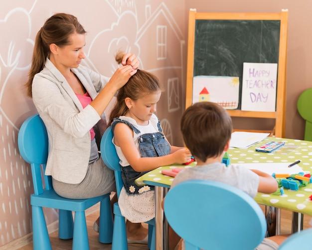 Учитель среднего кадра завязывает девушке волосы