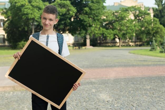 Medium shot teenage boy holding  black board