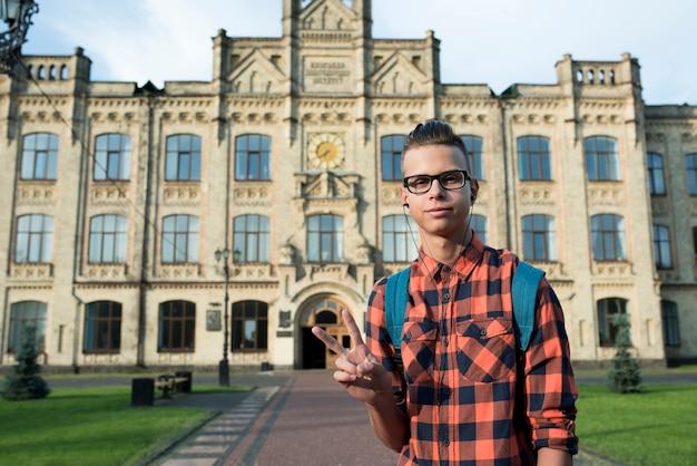 Medium shot teenage boy showing peace sign