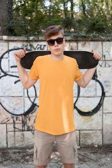 Ragazzo adolescente colpo medio con lo skateboard
