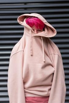 Adolescente del tiro medio che indossa maglia con cappuccio rosa