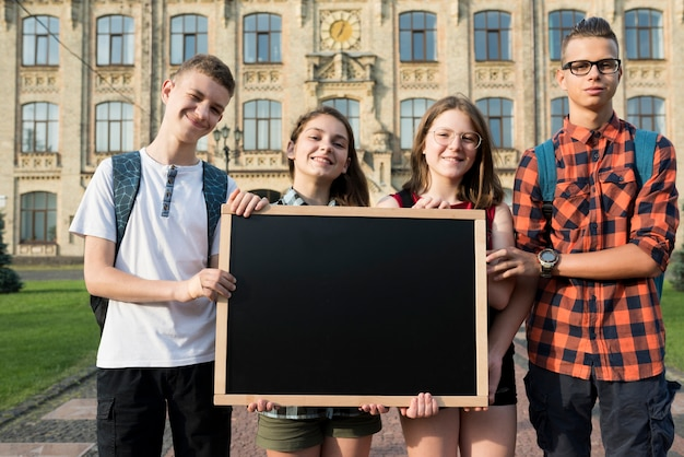 Medium shot teenagers holding blackboard