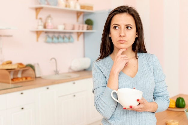 Средний выстрел думая женщина с белой чашкой