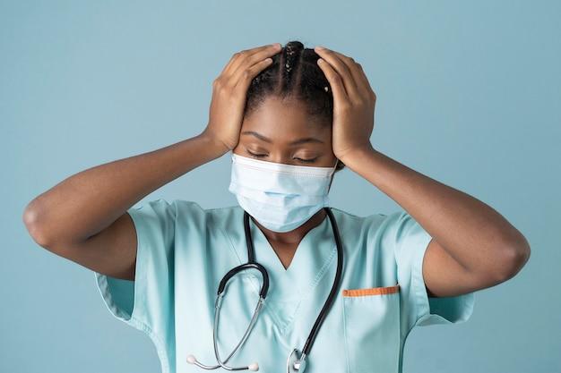 Средний снимок усталого доктора в маске