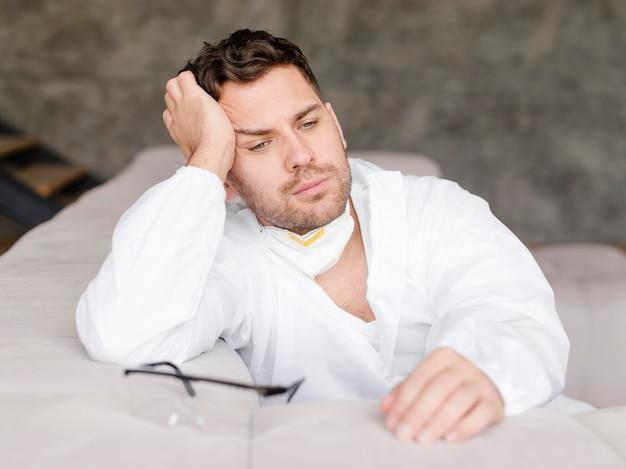 Uomo stanco del colpo medio che si siede sul sofà
