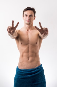 Medium shot topless man gesturing peace sign
