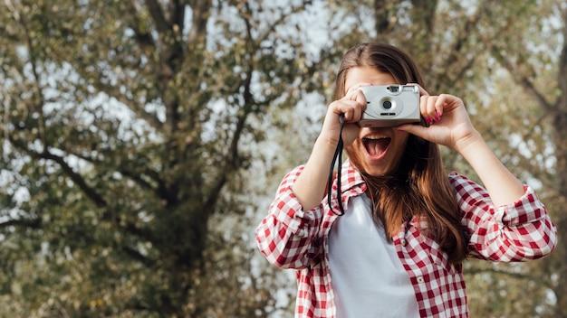 Medium shot of traveler taking a photo