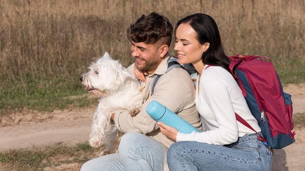 Viaggiatori di tiro medio che tengono cane
