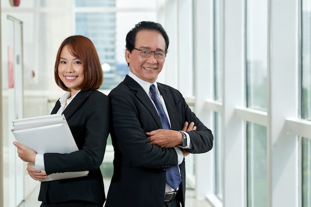 Medium shot of two asian colleagues standing back to back with their arms folded