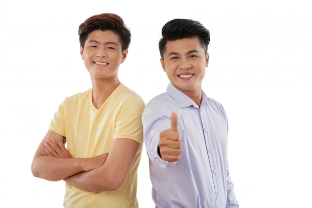 Medium shot of two guys standing shoulder to shoulder and gesturing at camera
