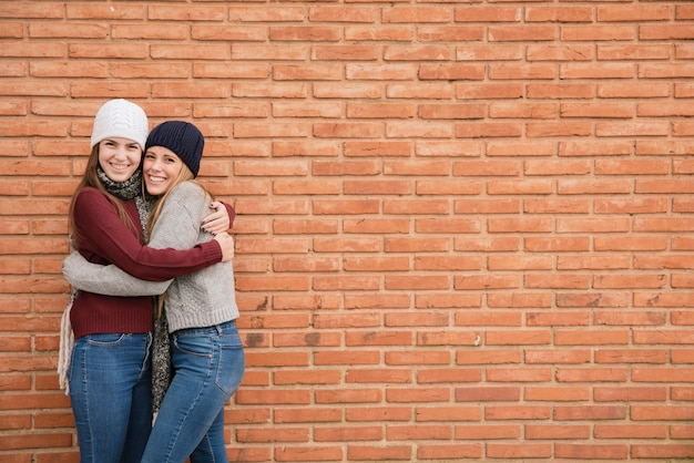 Medium shot two hugging young women in front of brick wall