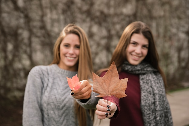 Medium shot of two smiling women holding leaves in their hands