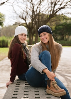 Medium shot of two smiling women sitting on a bench