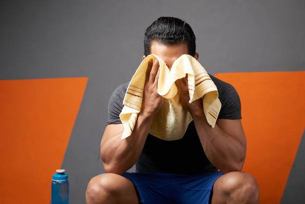 Medium shot of unrecognizable male athlete wiping sweat with a towel seated in gym changing room