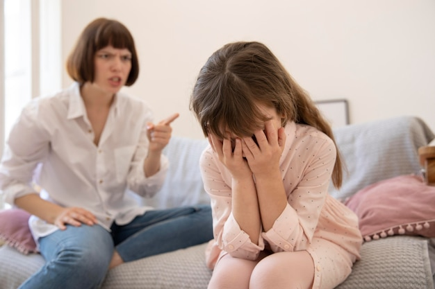 ミディアムショットの動揺した母親が娘を叱る