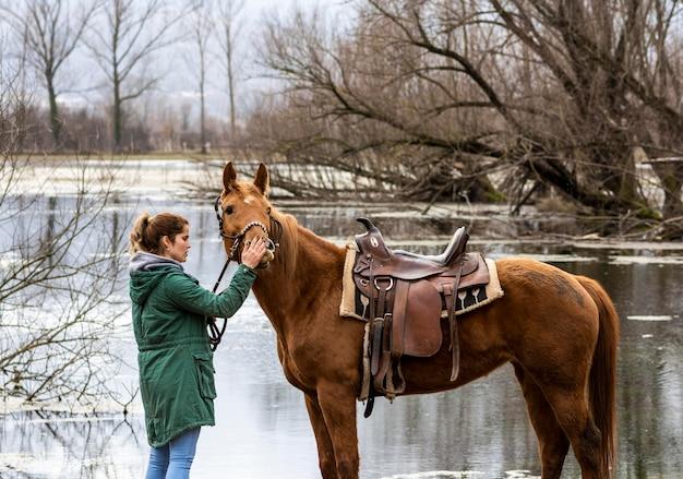 Женщина среднего роста и красивая лошадь