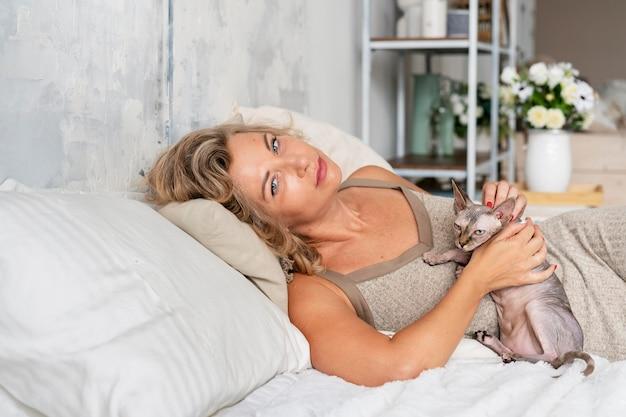 Женщина среднего кадра и кошка в постели