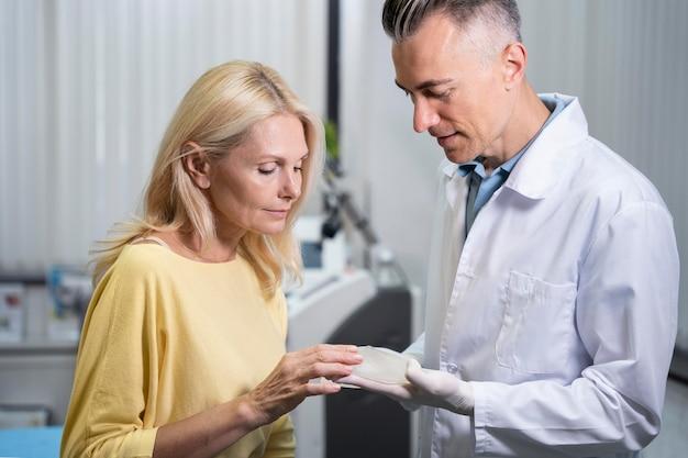 ミディアムショットの女性と医者が話し合う