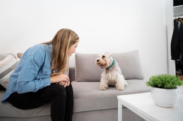 ミディアムショットの女性とソファの上の犬